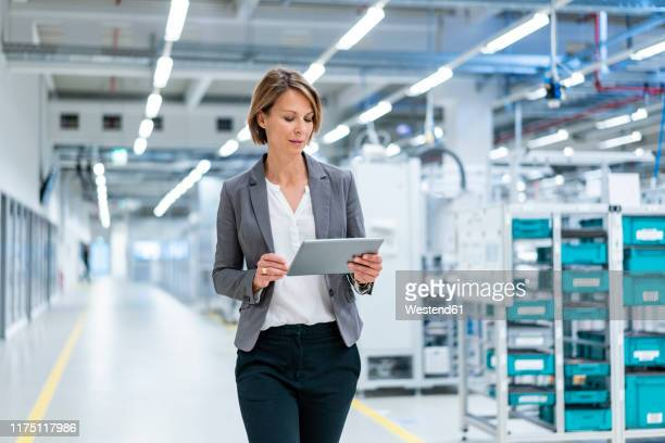 businesswoman with tablet in a modern factory - weibliche angestellte stock-fotos und bilder