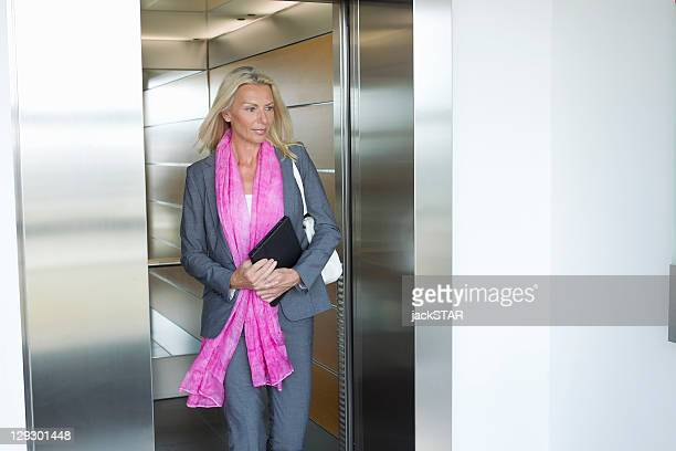 Businesswoman with tablet in elevator