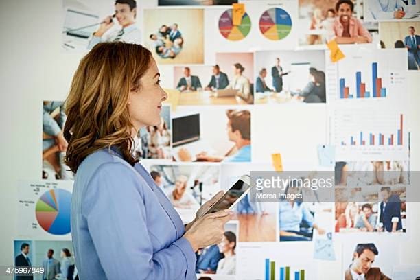 Businesswoman with tablet looking at images