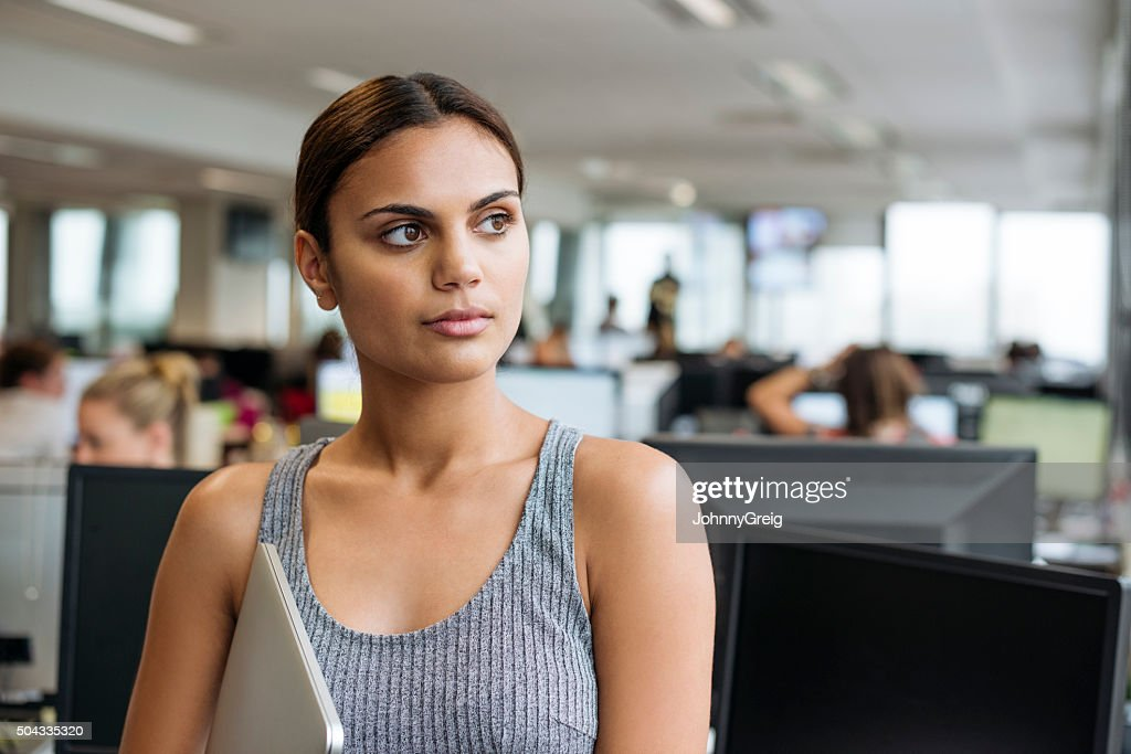 Businesswoman with tablet looking away in modern office : Stock Photo