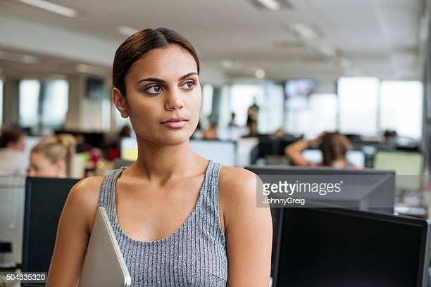 Businesswoman with tablet looking away in modern office