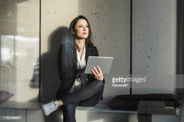 businesswoman with tablet sitting in lounge area in office - geschäftskleidung stock-fotos und bilder