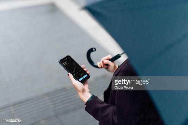 businesswoman with umbrella, checking stock market on smart phone in the rain - finance stock pictures, royalty-free photos & images