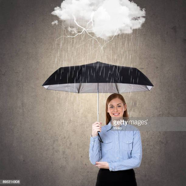 Businesswoman with umbrella under rain storm