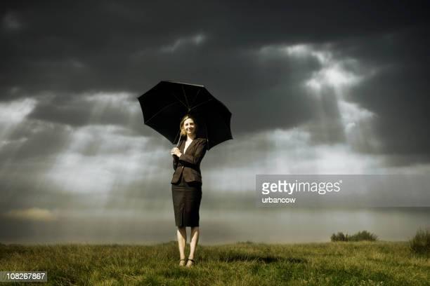 Geschäftsfrau mit Regenschirm unter stürmischen Himmel