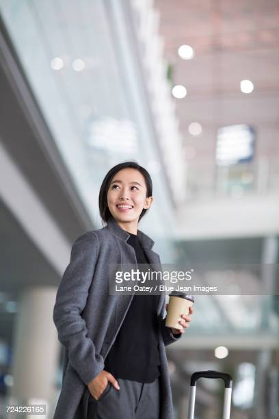 businesswoman with wheeled luggage in airport lobby - hands in pockets stock pictures, royalty-free photos & images