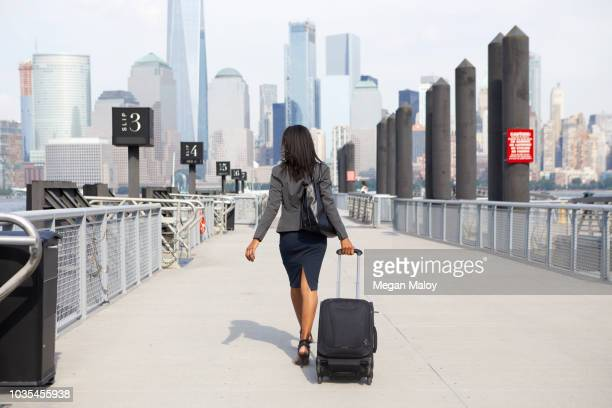 businesswoman with wheeled luggage on ferry pier - wheeled luggage stock photos and pictures