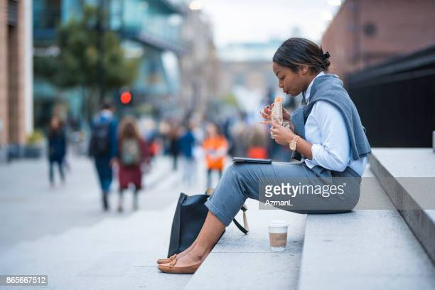 businesswoman working and eating sandwich - on the move stock pictures, royalty-free photos & images