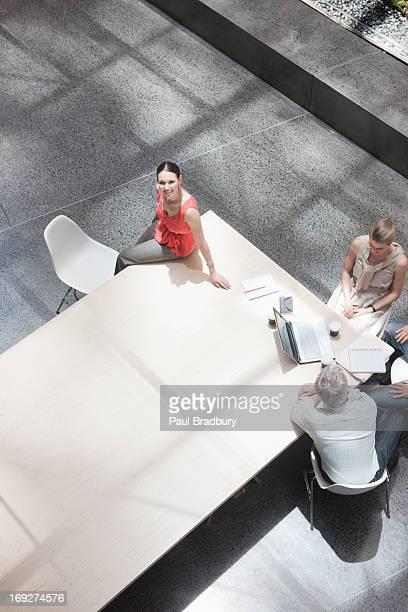 Geschäftsfrau working Abgesehen von Mitarbeitern am Konferenztisch