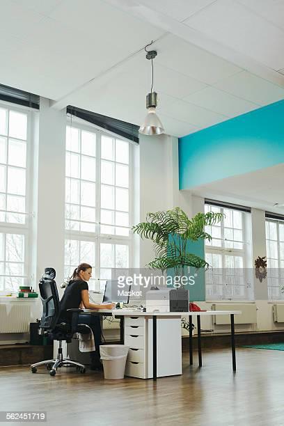 Businesswoman working at computer desk in creative workspace