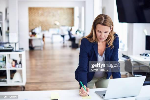 businesswoman working at desk in office - bürokleidung stock-fotos und bilder