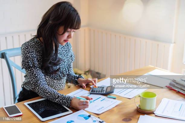 businesswoman working at desk in office - tax stock pictures, royalty-free photos & images