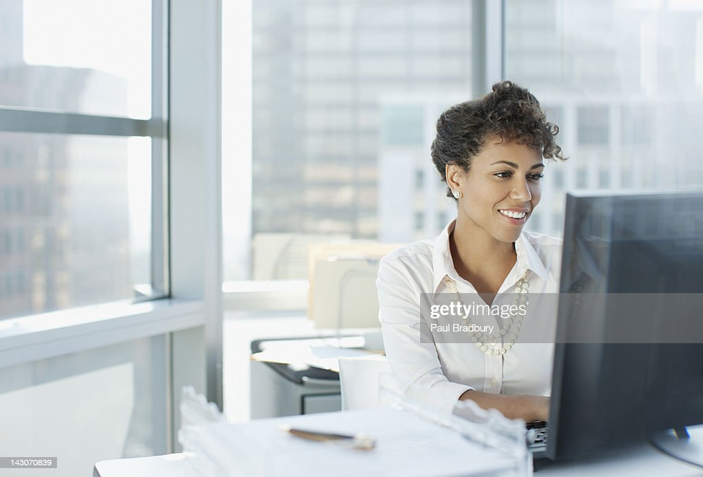 Businesswoman working at desk in office : Stock Photo