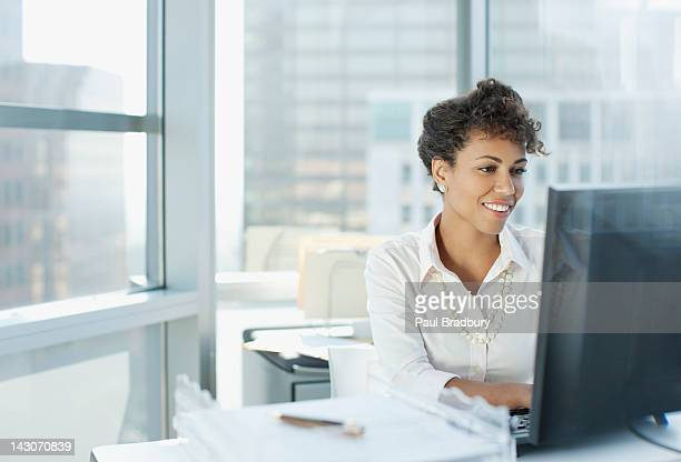 businesswoman working at desk in office - typen stockfoto's en -beelden