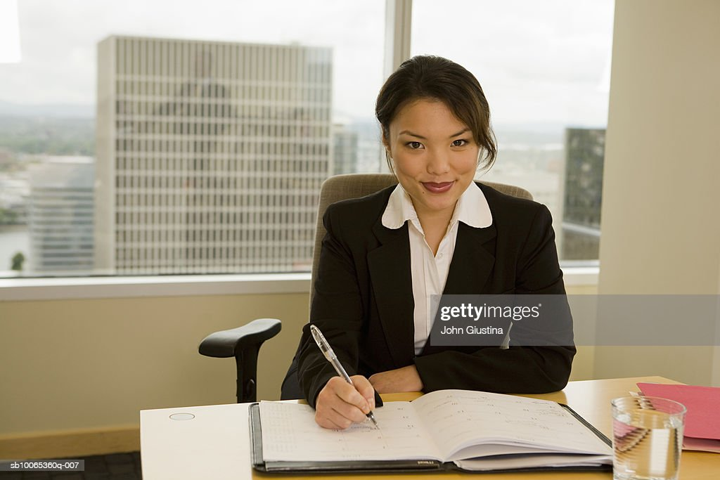 Businesswoman working at desk, smiling, portrait : Foto stock