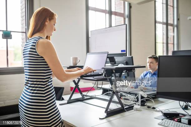 businesswoman working at ergonomic standing desk - stare in piedi foto e immagini stock