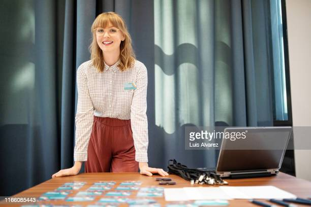 businesswoman working at front desk of convention center - formal stock pictures, royalty-free photos & images