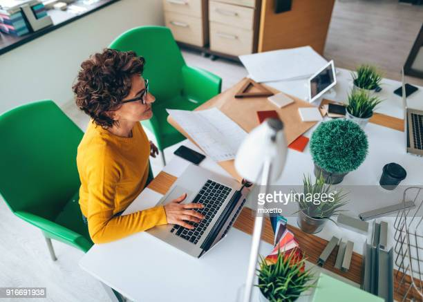 businesswoman working at her office desk with laptop - businesswear stock pictures, royalty-free photos & images
