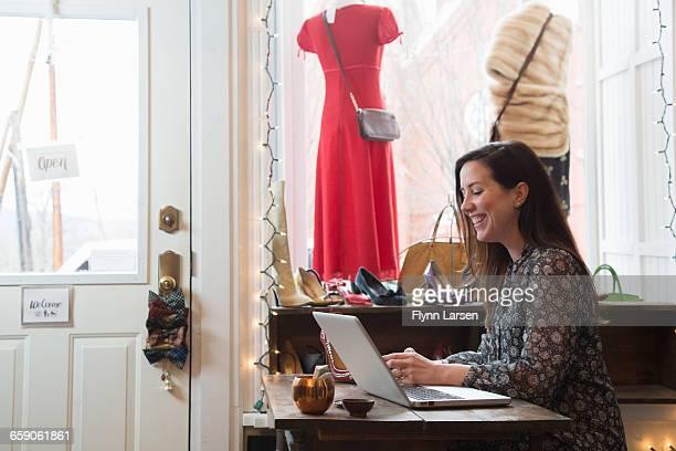 Businesswoman working at laptop in vintage shop
