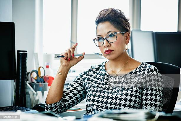 businesswoman working at office workstation - only mature women stock pictures, royalty-free photos & images