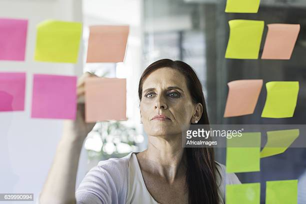 Businesswoman working from sticky notes.