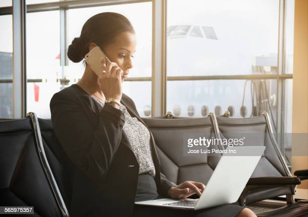 Businesswoman working in airport waiting area