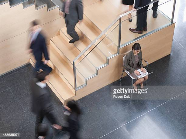 Businesswoman working in busy office corridor