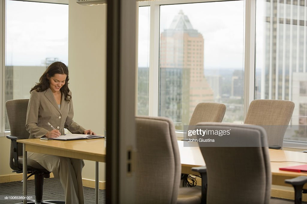 Businesswoman working in conference room, smiling : Foto stock
