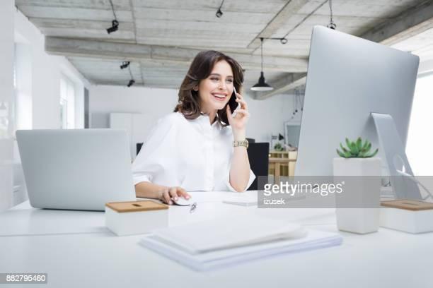 businesswoman working in modern workplace - donna in carriera foto e immagini stock
