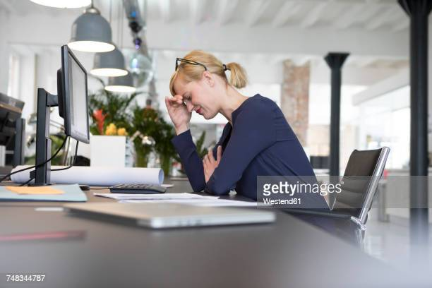Businesswoman working in office, being stressed out