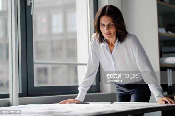 businesswoman working in office, looking at blueprints - 女性建築家 ストックフォトと画像