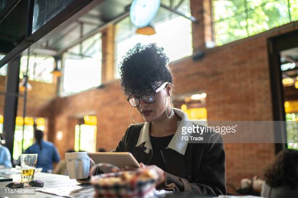 businesswoman working inside a restaurant, using digital tablet - part of a series stock pictures, royalty-free photos & images