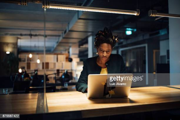 businesswoman working late on laptop - working late stock pictures, royalty-free photos & images