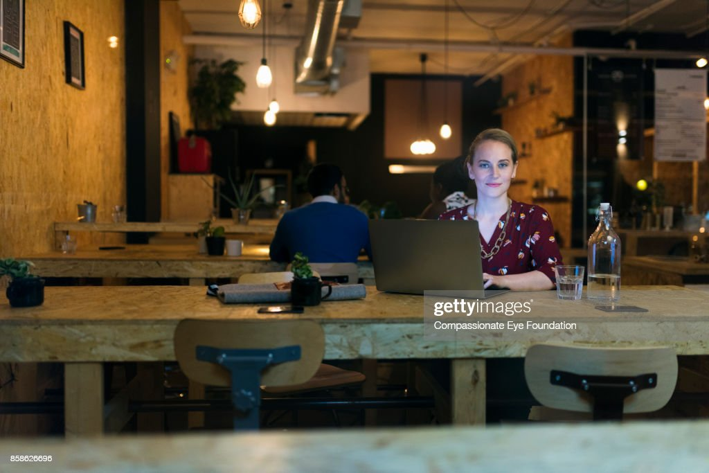 Businesswoman working late using laptop in cafe : Stock-Foto