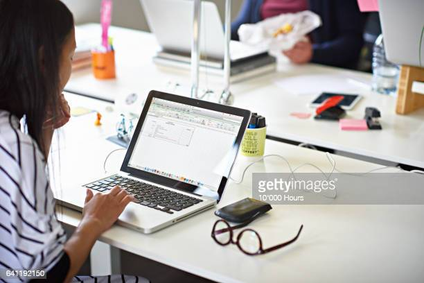 Businesswoman working on a laptop in hot desking start-up office