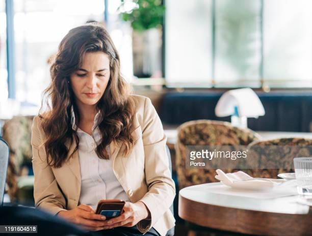 geschäftsfrau arbeitet an einem smartphone in einem restaurant - frauen über 30 stock-fotos und bilder