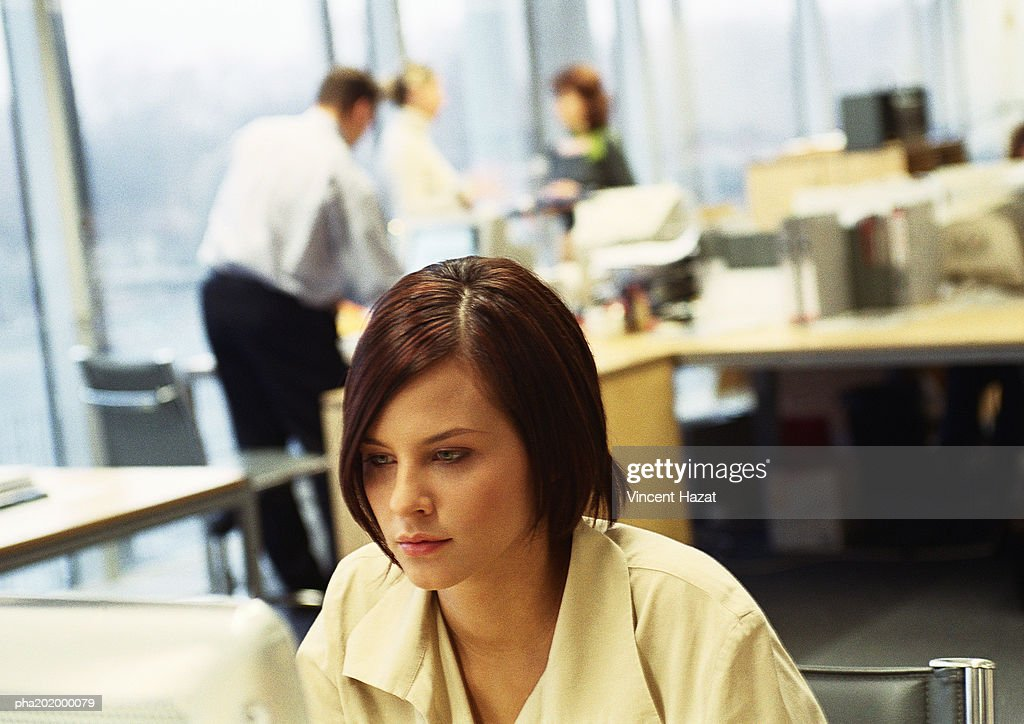 Businesswoman working on computer, business people working in background. : Stockfoto