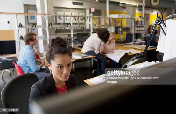 businesswoman working on computer in busy office - opgestoken haar stockfoto's en -beelden