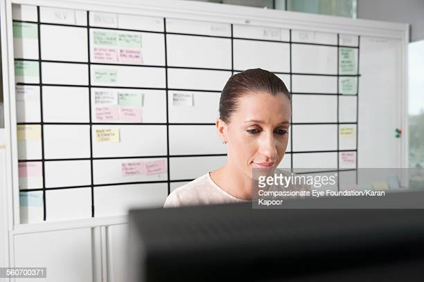 businesswoman working on computer in office - オールバック ストックフォトと画像