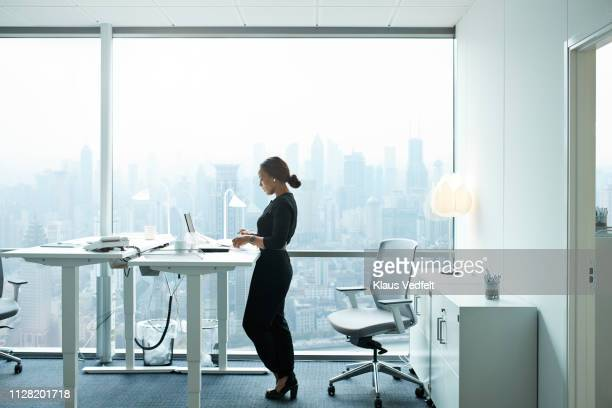 businesswoman working on computer in office with beautiful view of skyline - staan stockfoto's en -beelden