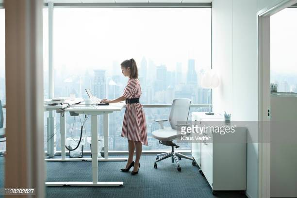 businesswoman working on computer in office with beautiful view of skyline - red dress fotografías e imágenes de stock
