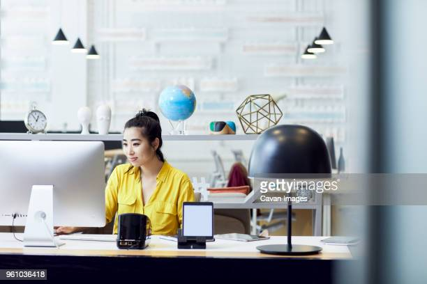 businesswoman working on desktop computer while sitting at desk in creative office - one world stock pictures, royalty-free photos & images
