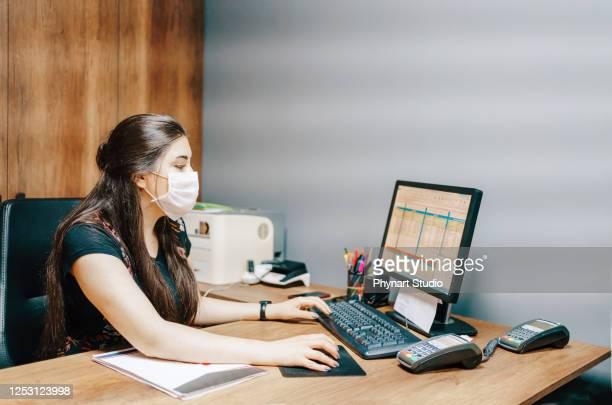 フェイスマスクを着用しながらデスクトップpcで作業するビジネスウーマン - state of emergency ストックフォトと画像