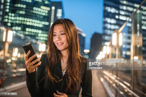 夜にデジタルタブレットで働いているビジネスウーマン - 30代の女性 ストックフォトと画像