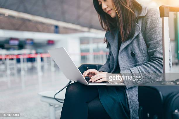 Businesswoman working on her laptop at airport.