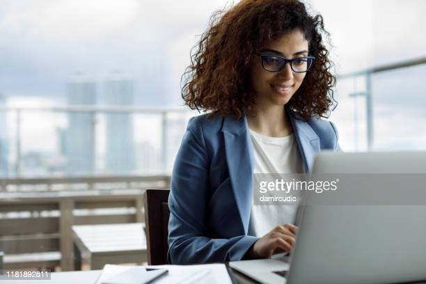 businesswoman working on laptop at a cafe - the internet stock pictures, royalty-free photos & images