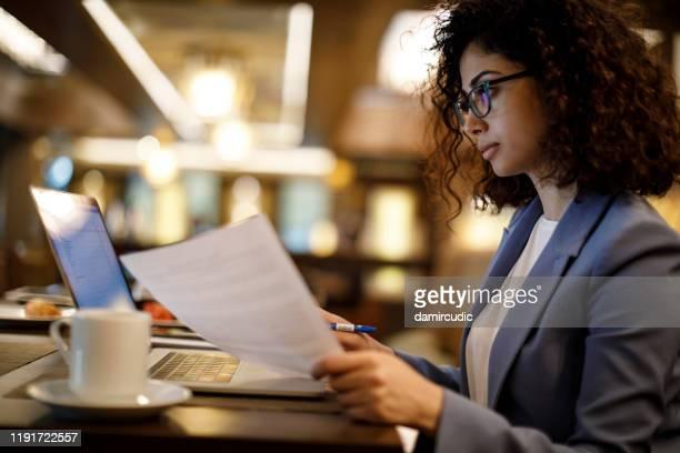 geschäftsfrau arbeitet am laptop in einem café - rechnungswesen stock-fotos und bilder