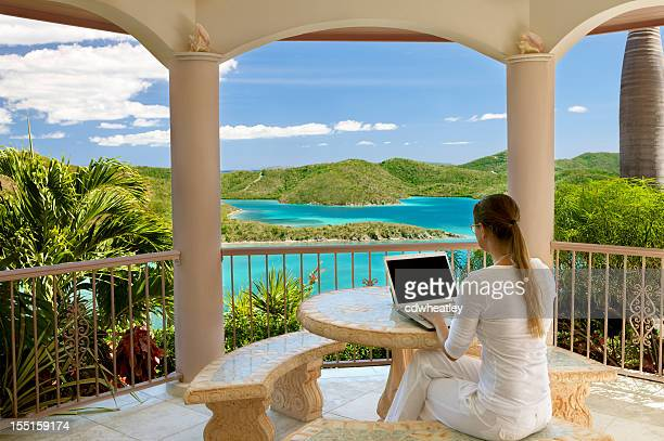 businesswoman working on laptop at vacation villa in the Caribbean