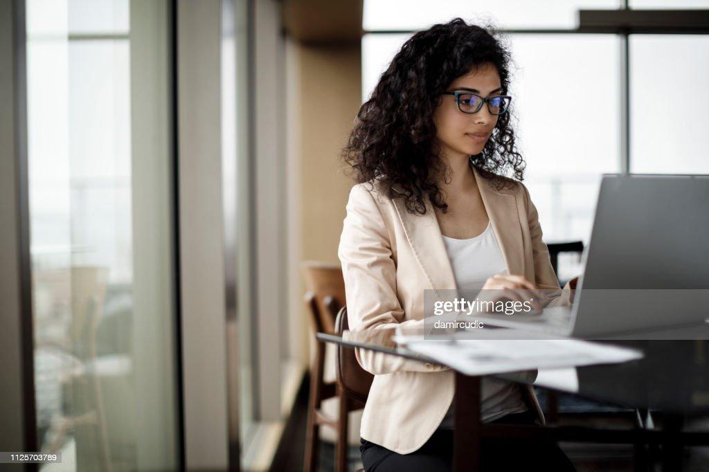 Businesswoman working on laptop in a coffee shop : Foto stock