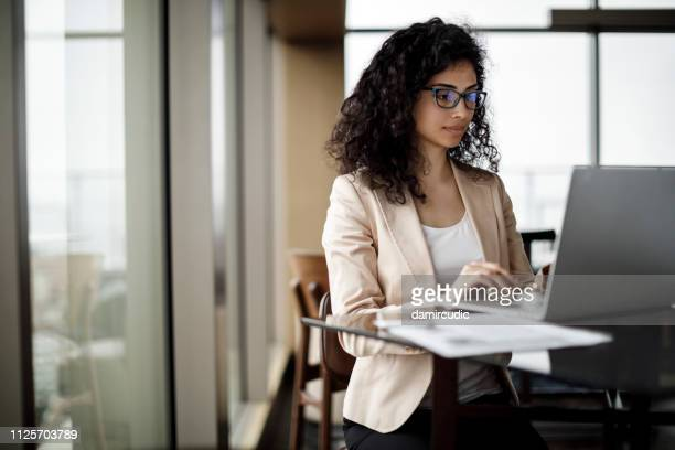 businesswoman working on laptop in a coffee shop - computer software stock pictures, royalty-free photos & images